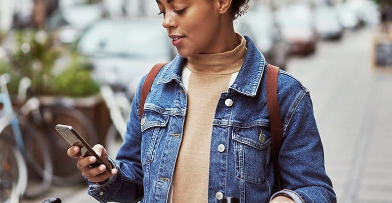 a woman looks at a financial app on her phone