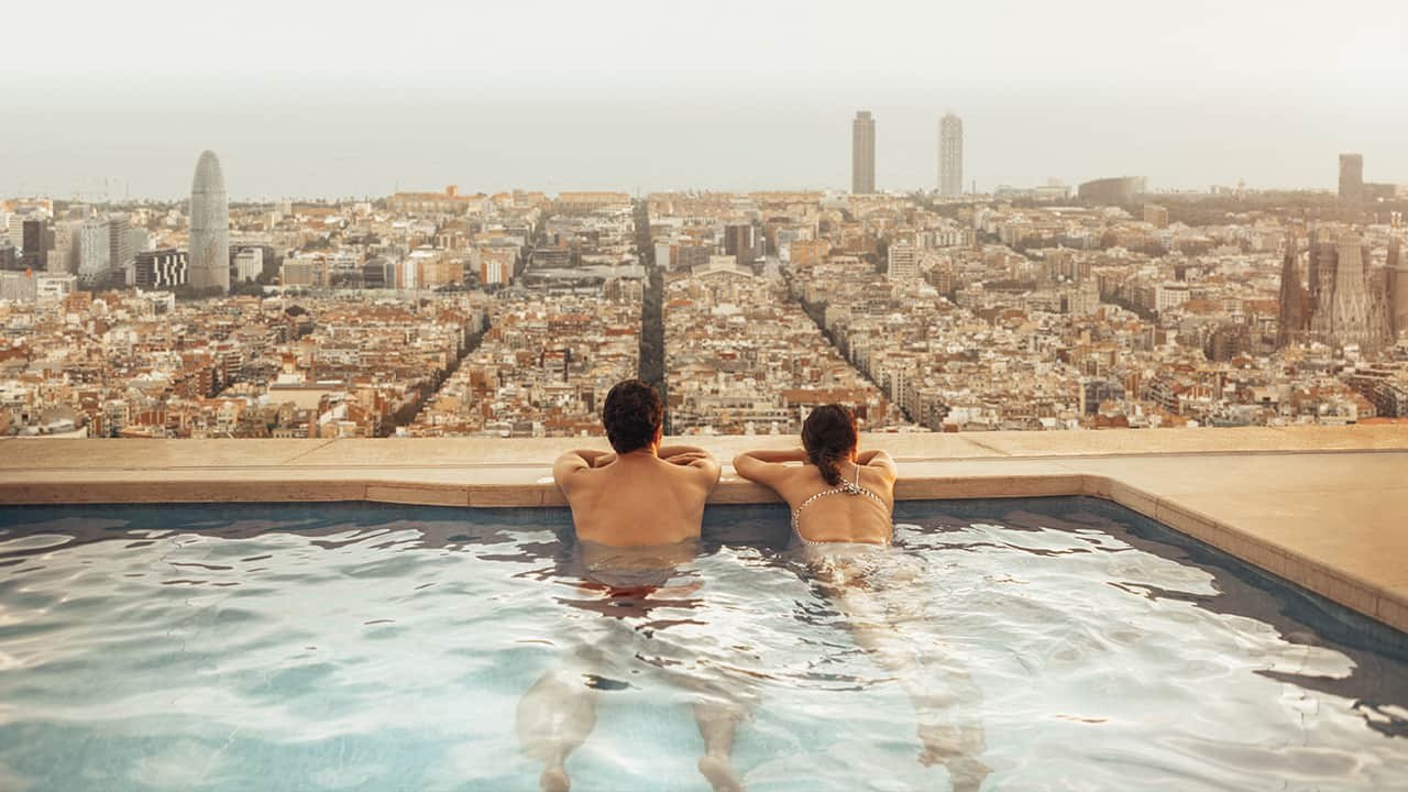 a couple enjoy the view from a rooftop pool