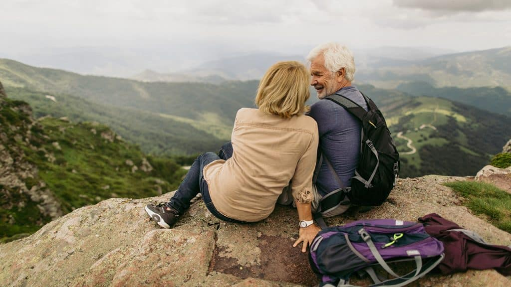 a mature couple cuddle during a hike