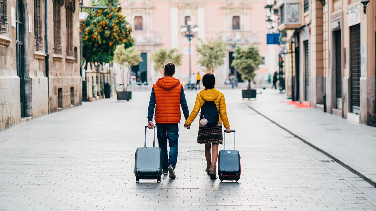 a traveling couple walks hand in hand