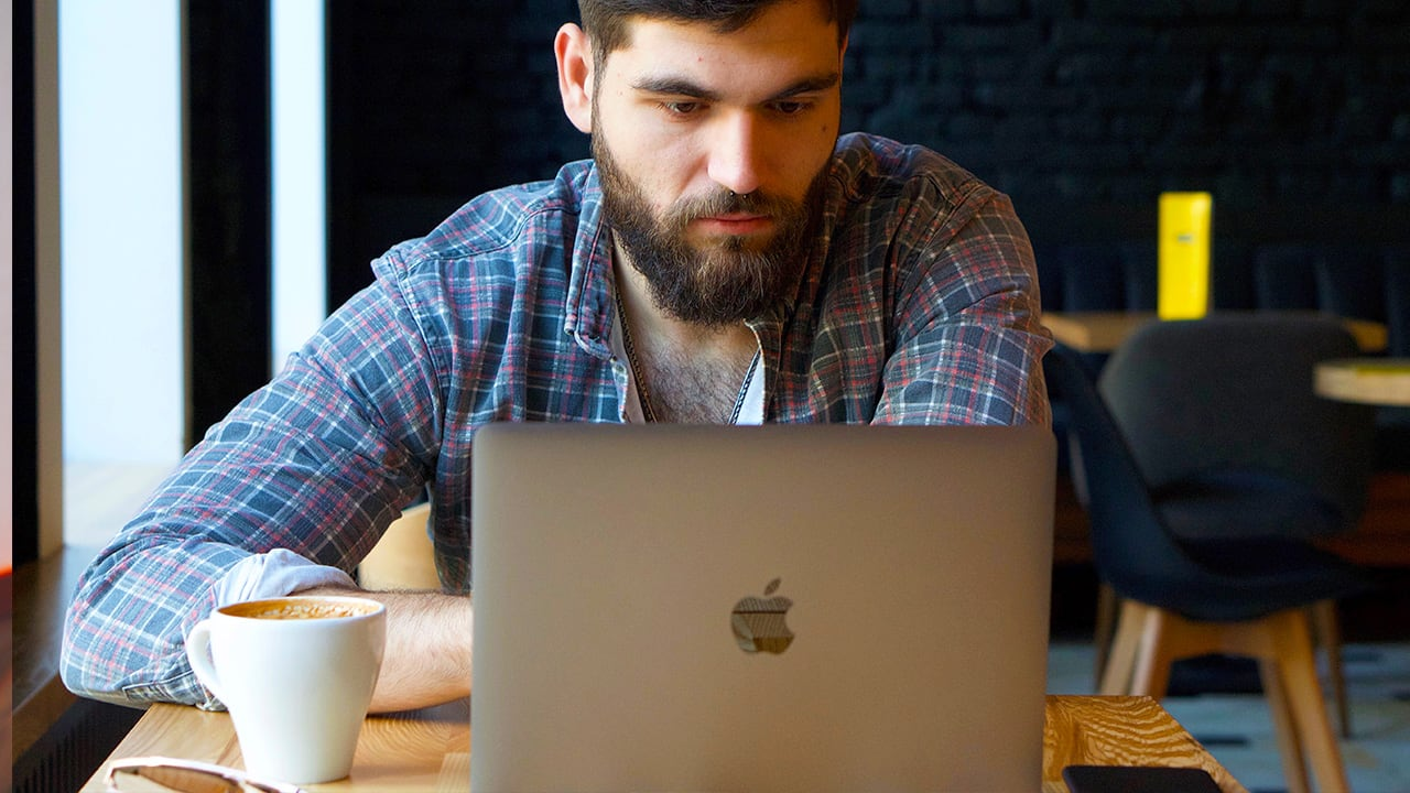 man looks at the screen of a macbook