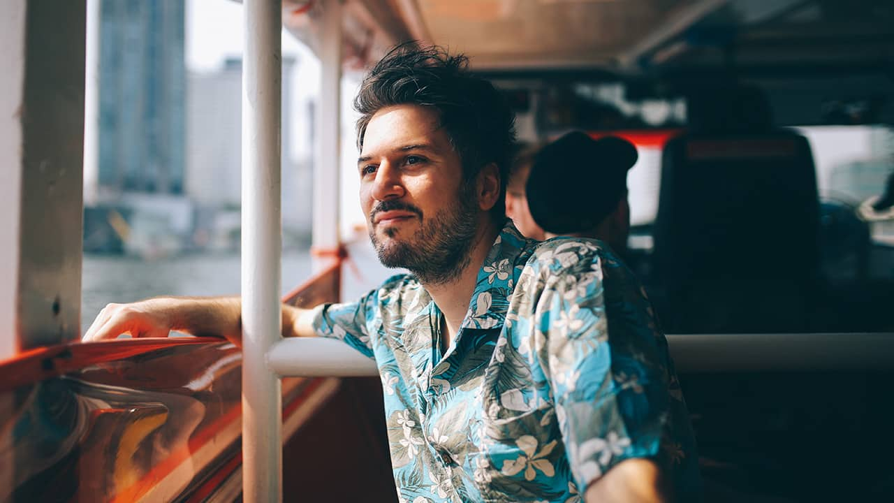 man looks out the window of tour bus