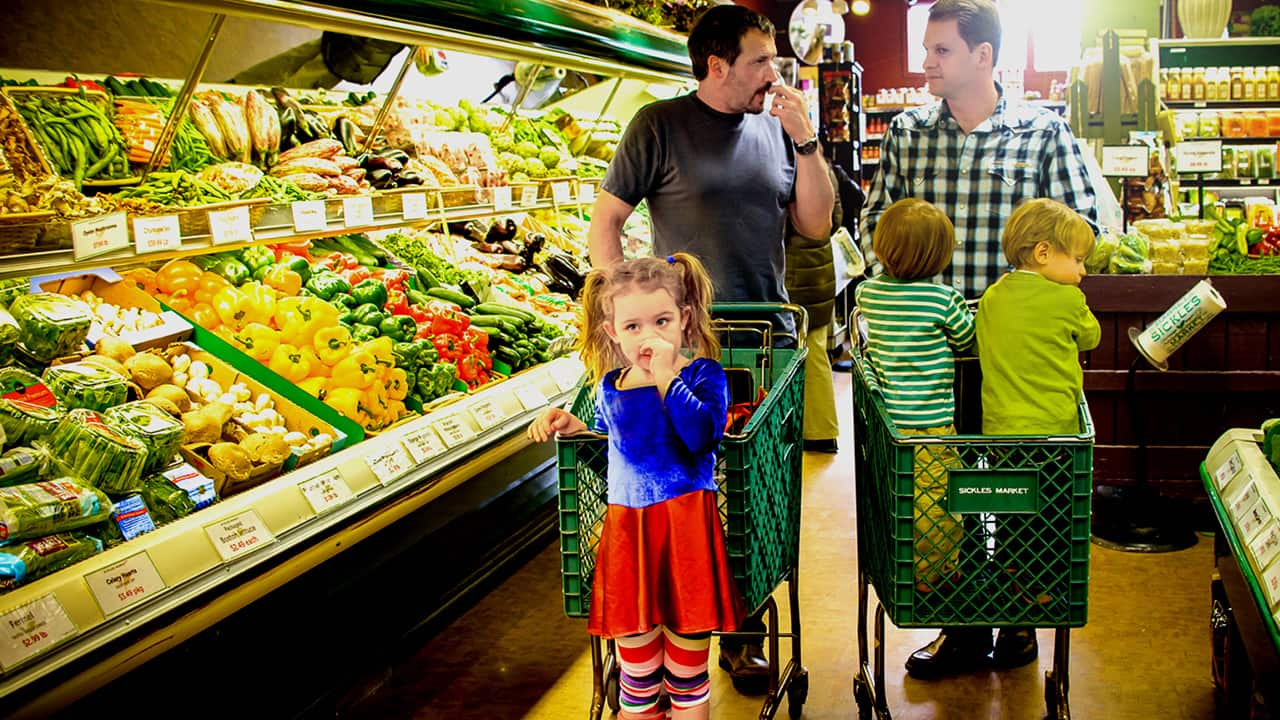 families at supermarket produce section