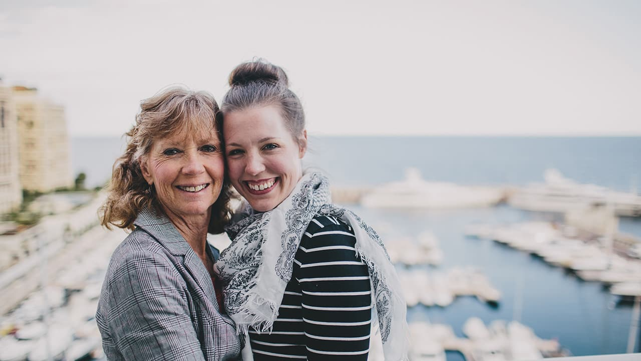 mother and daughter pose in front of a scenic view