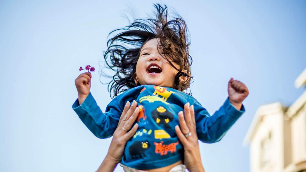a happy baby is being tossed into the air