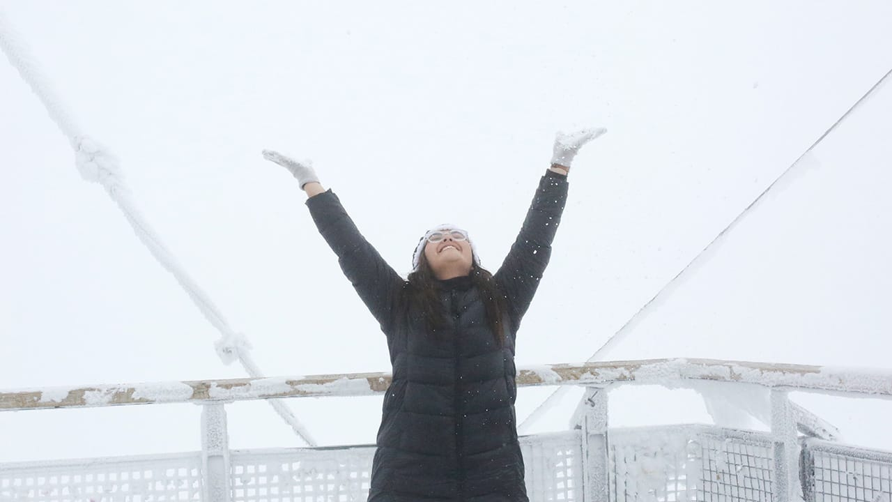 woman celebrates on a ship during cold weather