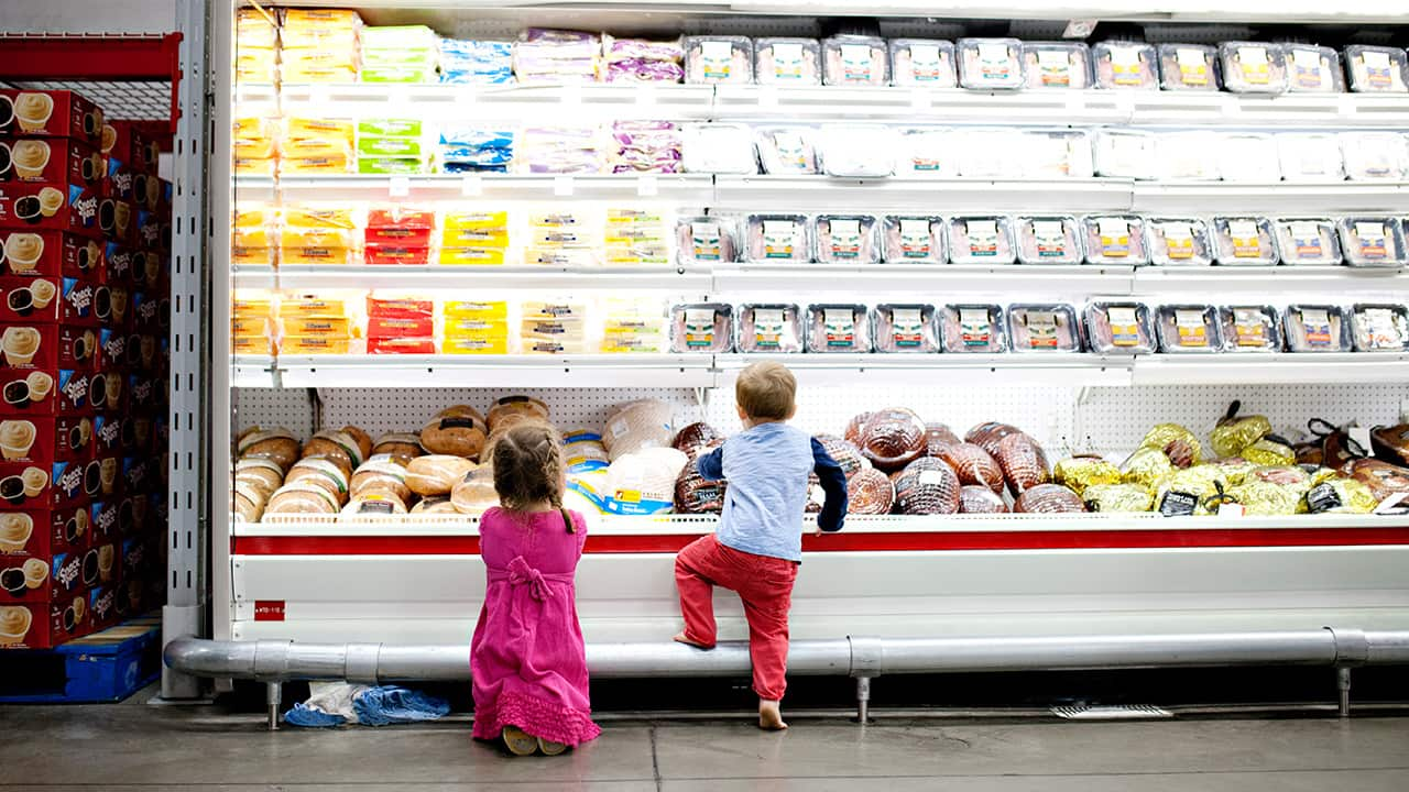 children in the meat aisle of supermarket