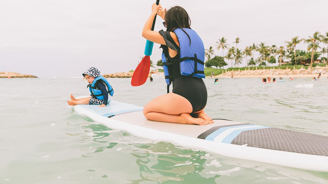 mother and baby paddle board in the ocean