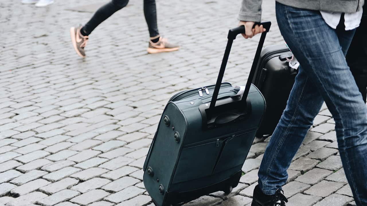 carrying suitcase through a city