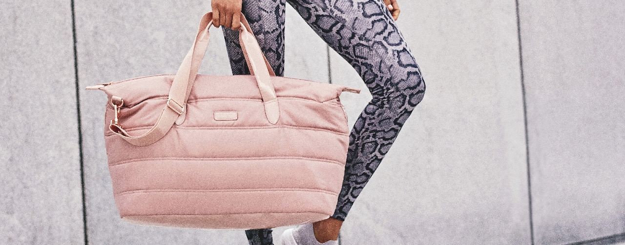 girl in athletic gear holding a FLY Weekender Bag in Blush Pink