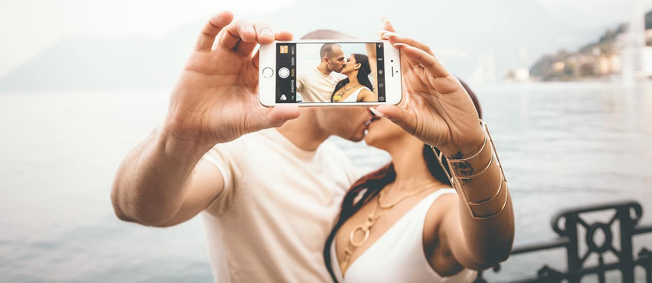 couple taking romantic selfie pics while kissing