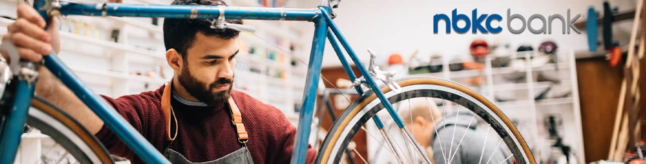 Bike shop owner working on vintage bicycle with NBKC logo